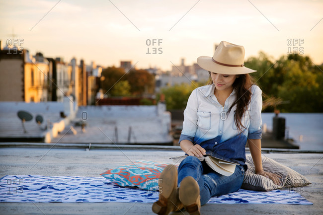Woman relaxing with a book on a rooftop