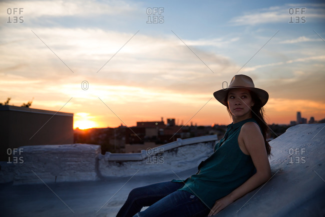 Woman resting on a rooftop at sunset