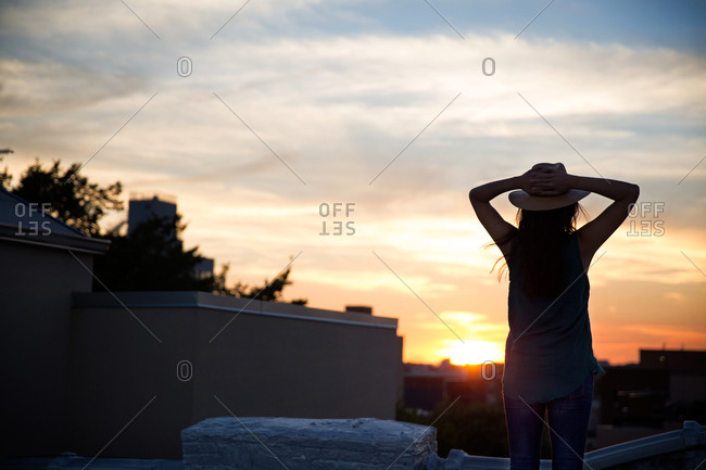 Woman watching the sunset on a rooftop