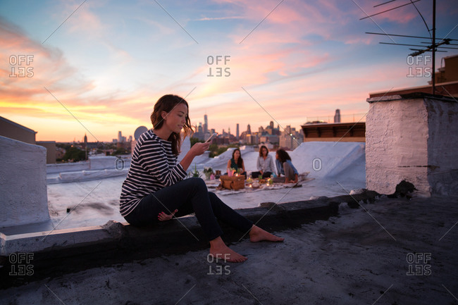 Young woman checking her smartphone on a rooftop in Brooklyn