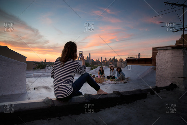 Woman taking a picture of her friends on a rooftop in Brooklyn