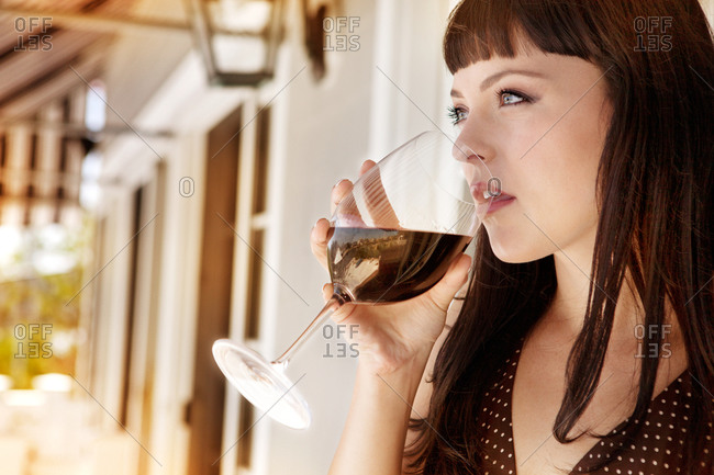 Woman drinking red wine on porch