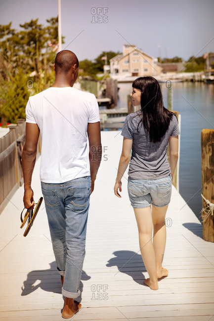 Young couple walking along wooden dock towards French flag