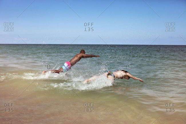 Couple on vacation jumping into the surf