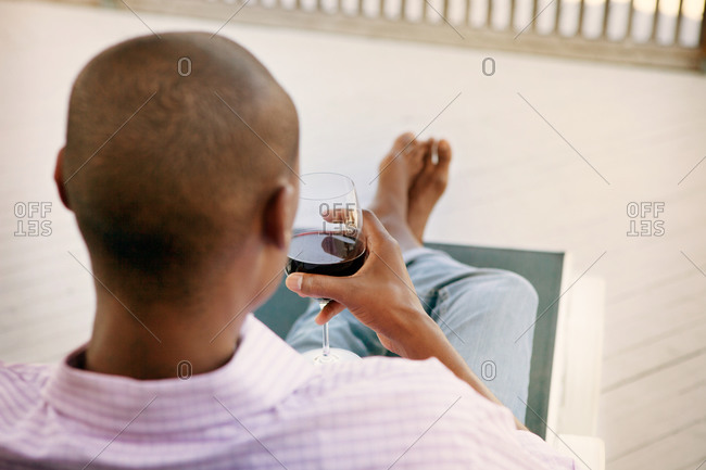 Man drinking wine on the porch