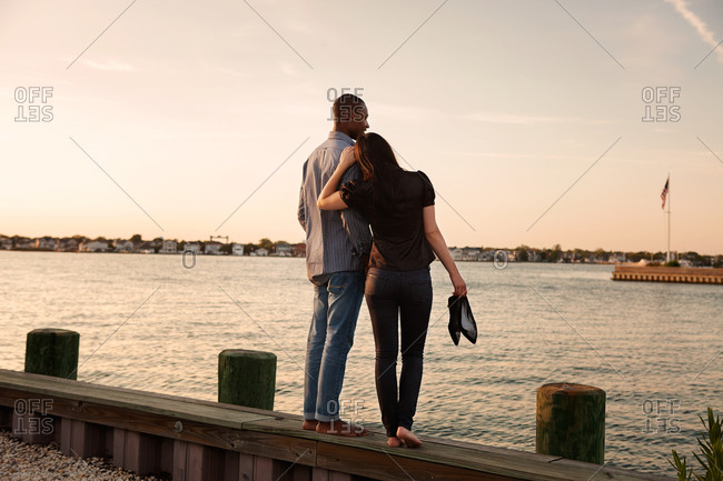 Couple standing together on a wooden seawall
