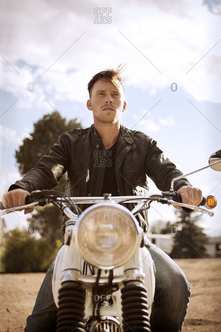 Man in leather jacket sitting on motorcycle