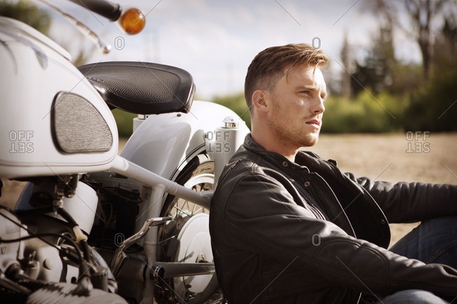 Man in leather jacket leaning against motorcycle