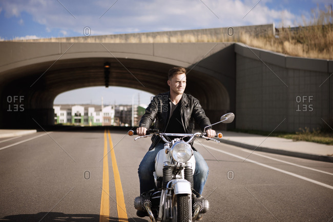 Man in leather jacket riding motorcycle