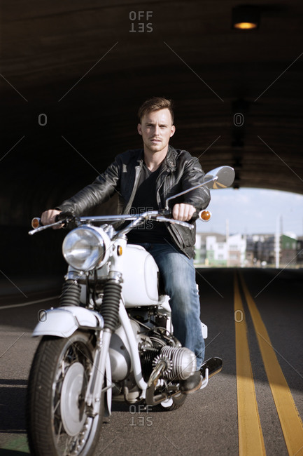 Man in leather jacket driving motorcycle