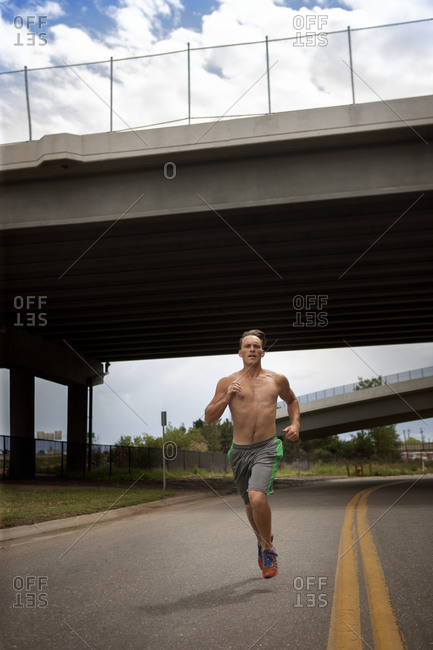 Young man jogging in the middle of the road