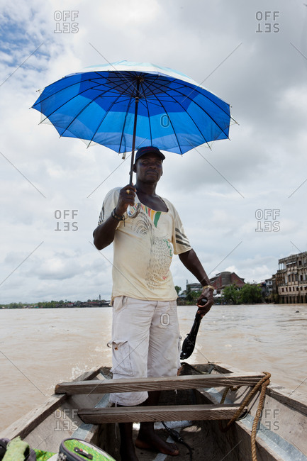 City of Quibdo, Choco Region, Colombia - September 27, 2012: A man covers from the sun with an umbrella while sailing his boat
