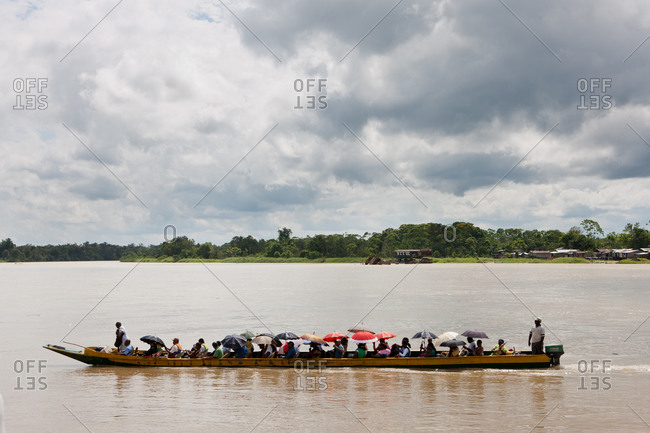 City of Quibdo, Choco Region, Colombia - September 27, 2012: A group of people crossing River Atrato on a motor boat