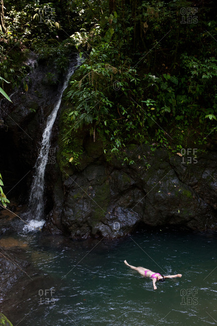 Choco Region, Nuqui, Colombia - October 1, 2012: Woman swimming by a waterfall