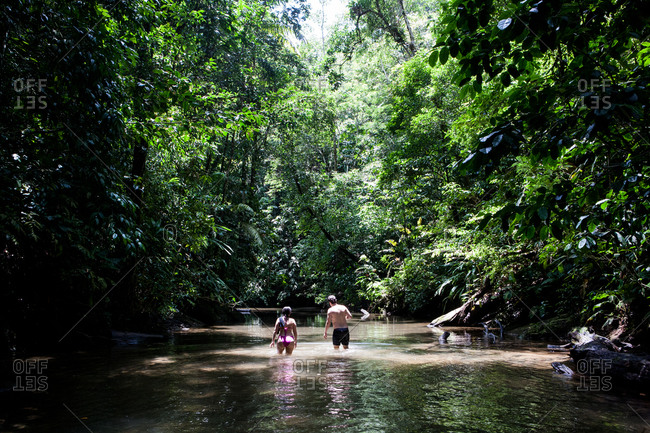 Couple walking on a river in the jungle