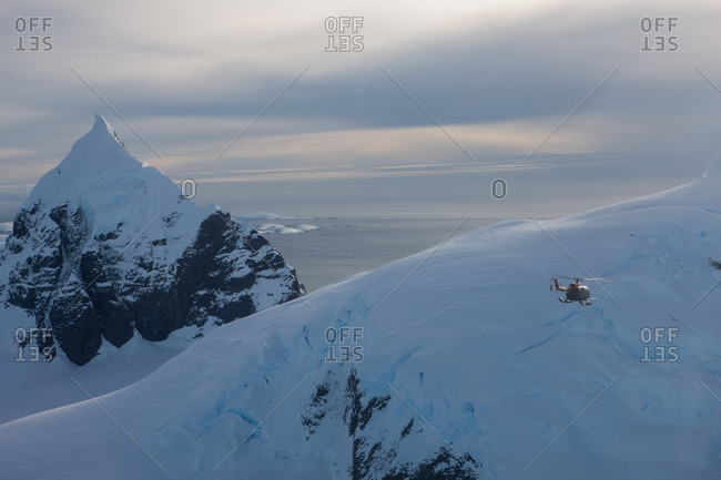 A helicopter flying over a the mountains in Antarctica