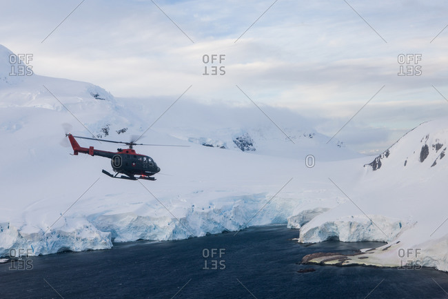 A helicopter flying over the sea and glaciers in Antarctica