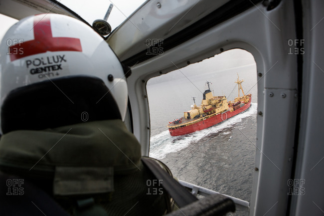 An Icebreaker is seen through the window of a helicopter