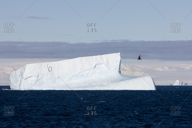 A helicopter flying over an iceberg