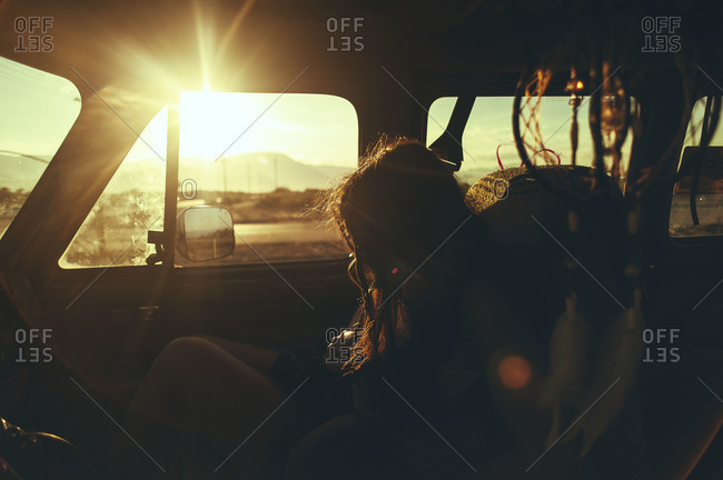 Woman in the front seat of a van at sunset