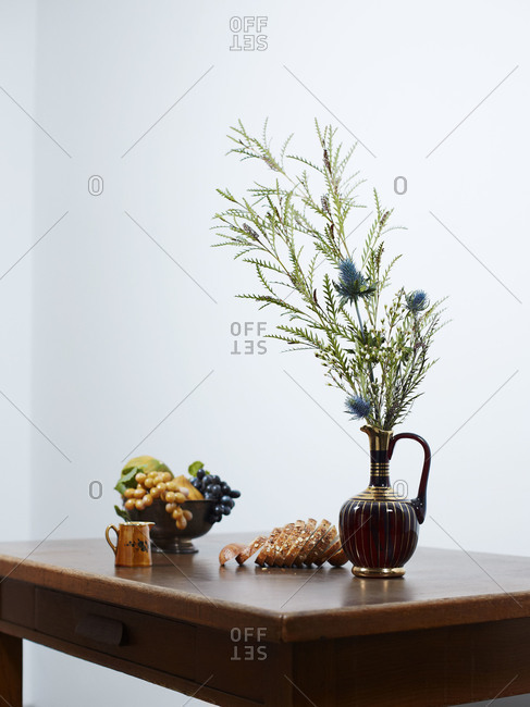 Still life of a flower bouquet with fruits and bread on a table