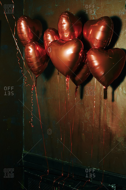 View of red heart-shaped balloons at a wall