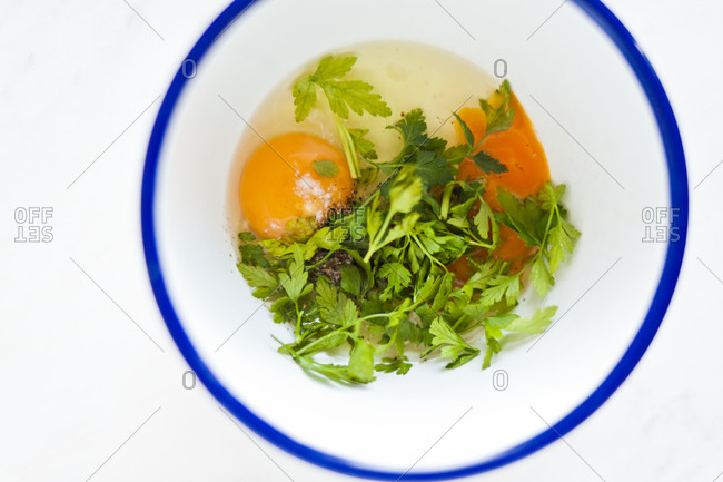 Eggs and herbs sit in a bowl