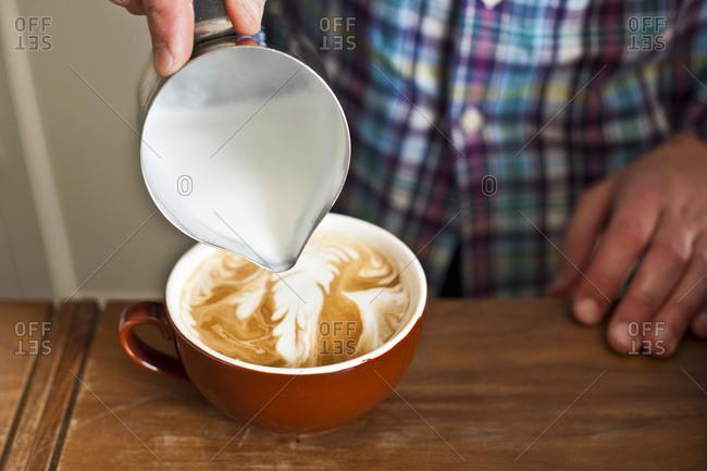 A man pours foam into coffee mug
