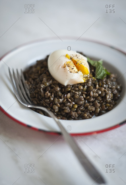 A lentil stew is topped with an egg