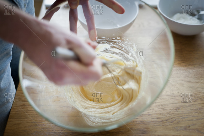 A cook whisks egg yolks and sugar into a cream