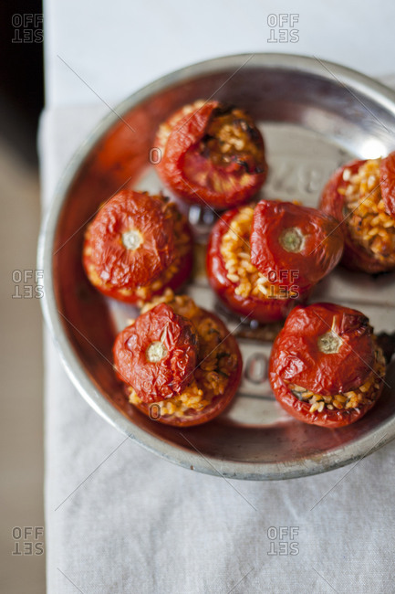 Stuffed tomatoes sit in a pan