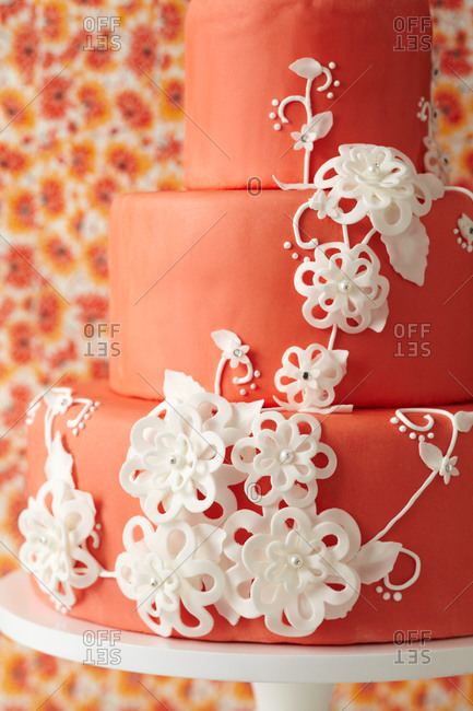 Red three-tiered cake decorated with white flowers