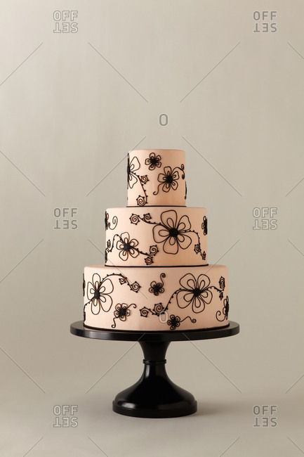 Black piping forms flowers on a three-tiered cake
