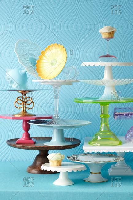 Multiple cake stands and two cupcakes stand on one another