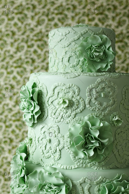 Green cake decorated with three dimensional flowers