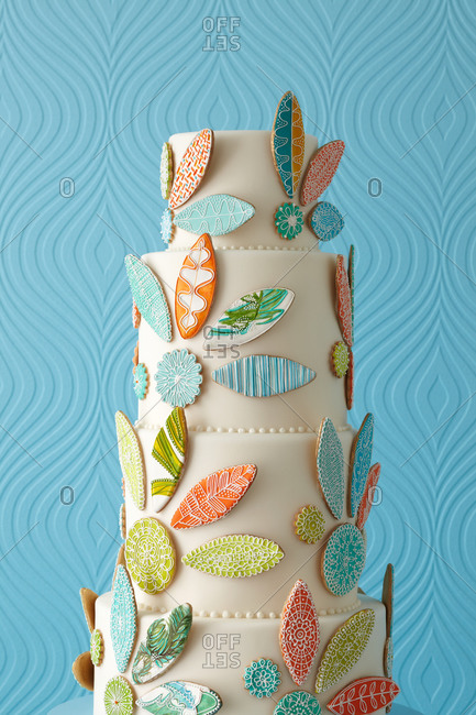 Abstract leaves decorate a white four-tiered cake