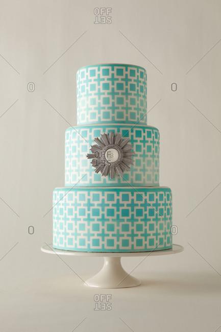 A sliver emblem decorates a three tier cake
