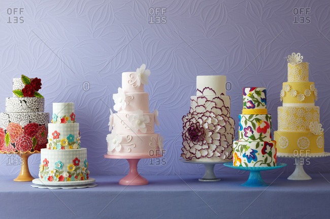 Six floral cakes on a counter