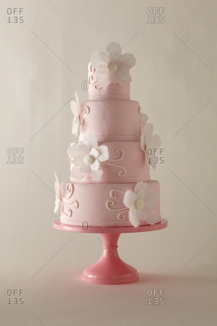 White flowers decorate a pink four-tiered cake