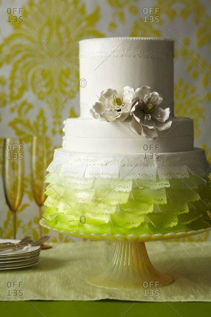 A three tiered cake sits in front of servingware
