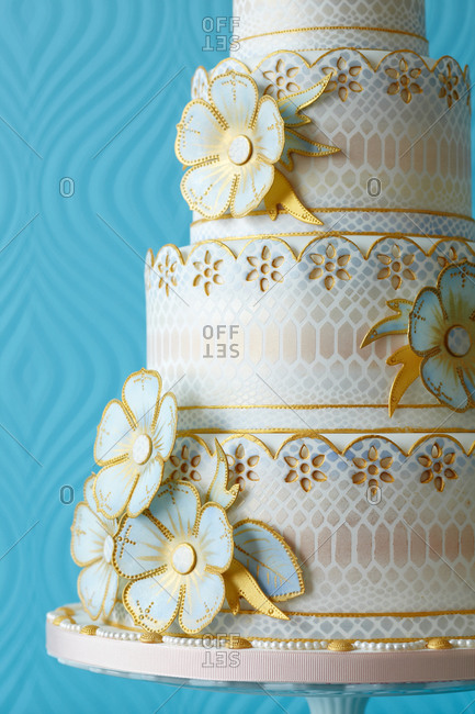 Close up of gold flowers on a four-tied cake