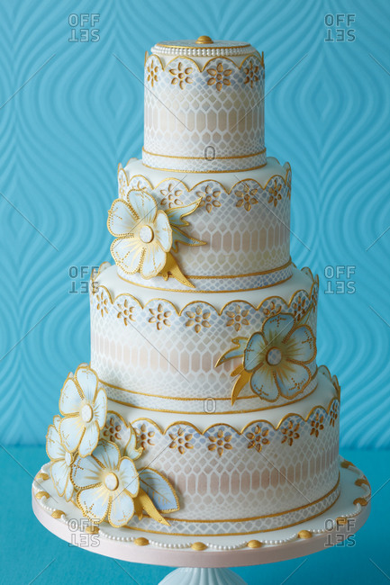 Flowers outlined in gold decorate a four-tiered cake