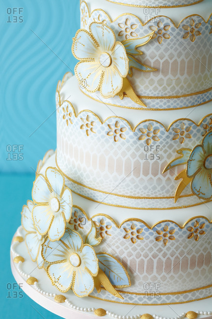Detail of flowers outlined in gold on a four-tiered cake