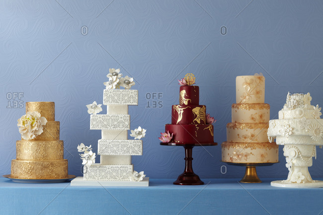 Five formal cakes sit on a counter