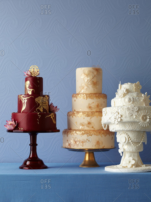 Three formal cakes sit on a counter