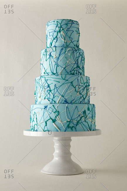 Piping splatters across a four-tiered cake