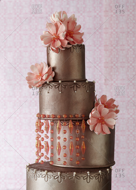 Pink flowers decorate a four-tiered cake