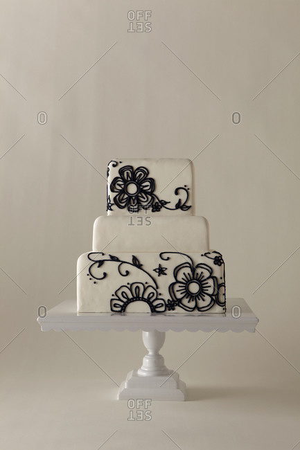 Black flowers decorate a white cake