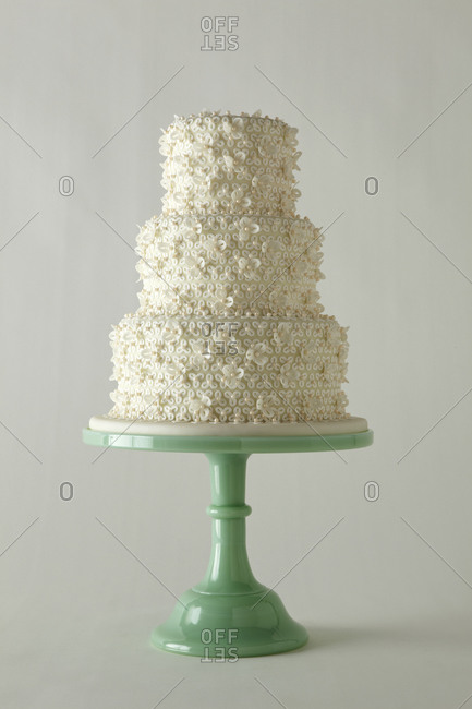 Three tiered cake decorated with tiny white flowers