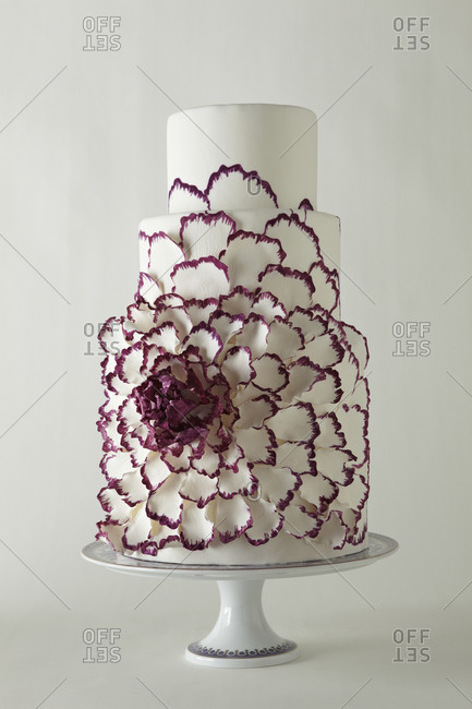 A large flower spreads across a four-tiered cake